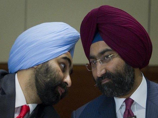 Managing Director of Fortis Healthcare Shivinder Singh speaks to his brother and Chairman Malivnder Singh during a news conference in Singapore