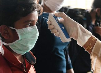 A government health worker in Kerala checks a boy's temperature