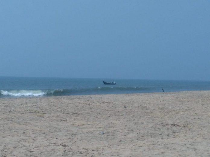 Malippuram beach, man fishing on small boat